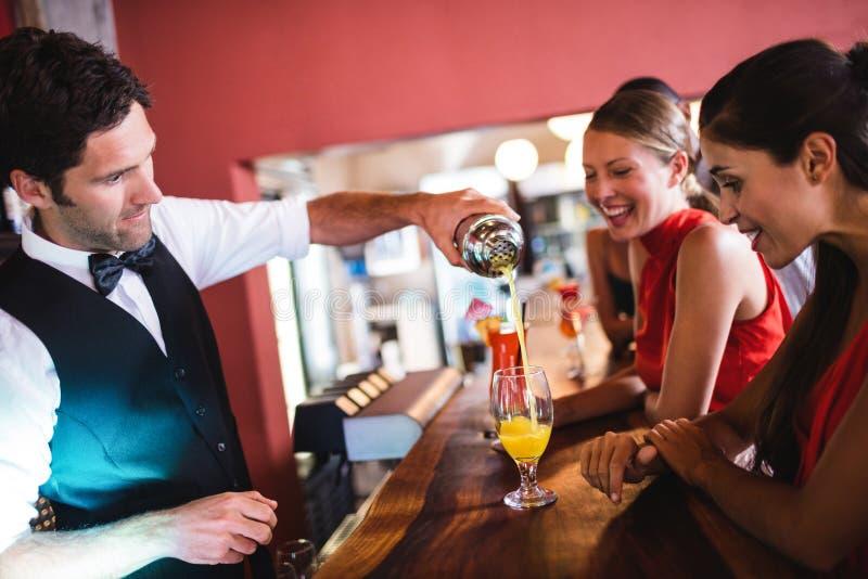 Hällande coctail för bartender i exponeringsglas på stångräknaren royaltyfri foto