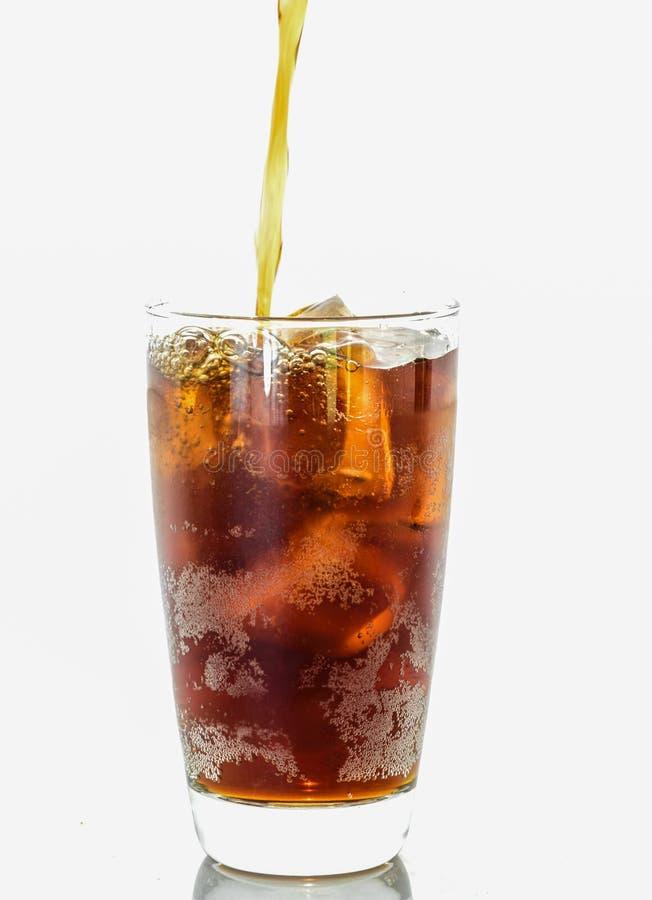 Hällande cola från flaskan arkivfoton