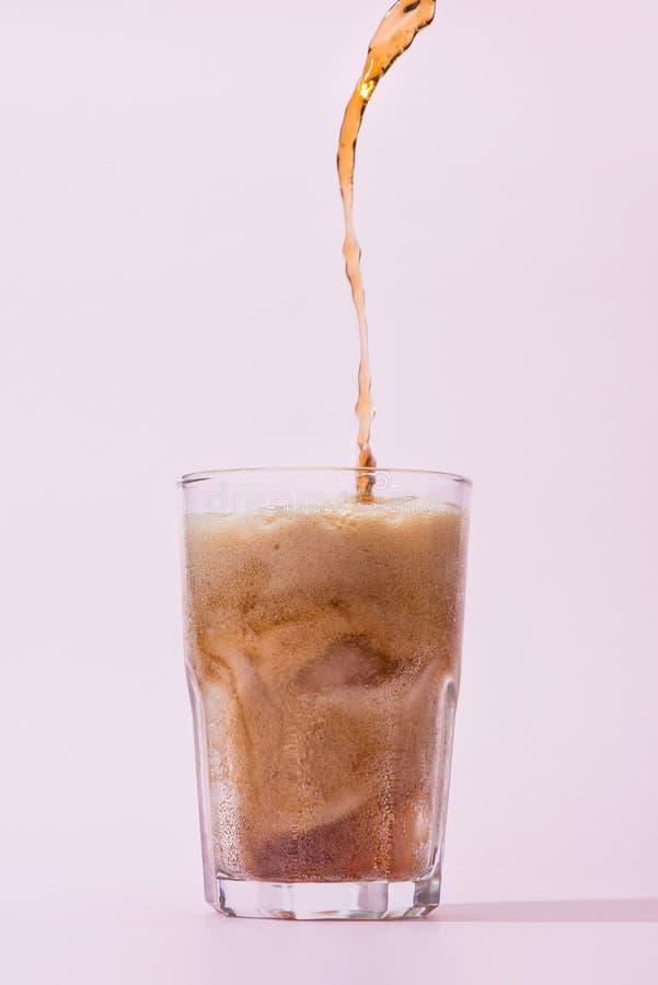 Hällande cola från flaskan in i exponeringsglas med att plaska arkivbild