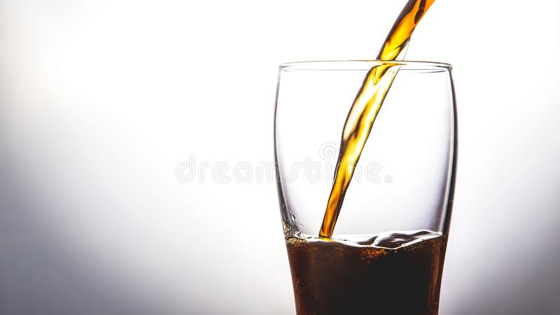 Hällande cola in i exponeringsglas med is på vitt bakgrundskopieringsutrymme royaltyfri fotografi