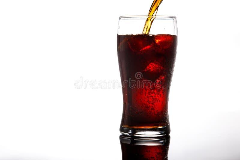 Hällande cola in i exponeringsglas med is på vitt bakgrundskopieringsutrymme royaltyfri bild