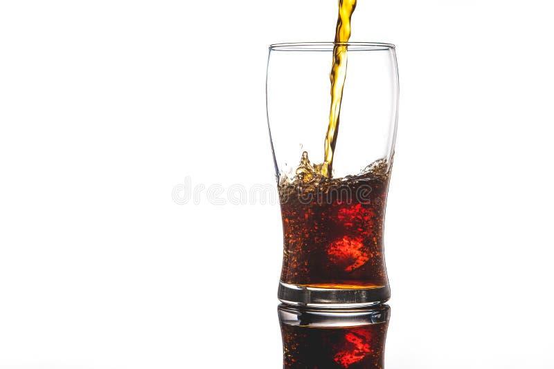 Hällande cola in i exponeringsglas med is på vitt bakgrundskopieringsutrymme royaltyfria bilder