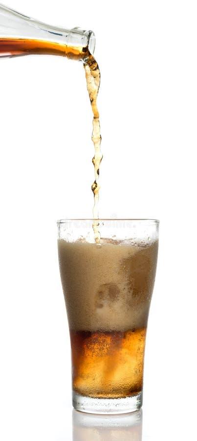 Hällande cola in i exponeringsglaset royaltyfria bilder