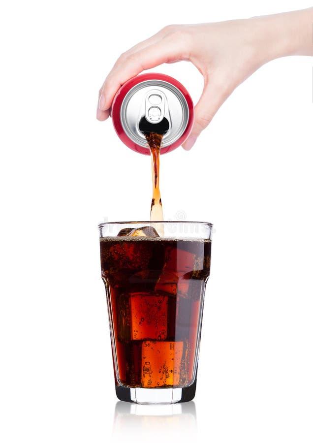 Hällande coladrink för kvinnlig hand från tenn till exponeringsglas arkivfoto
