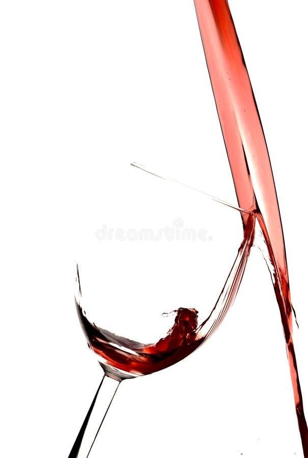 Hällande Cranberryfruktsaft i Wineexponeringsglas arkivbilder