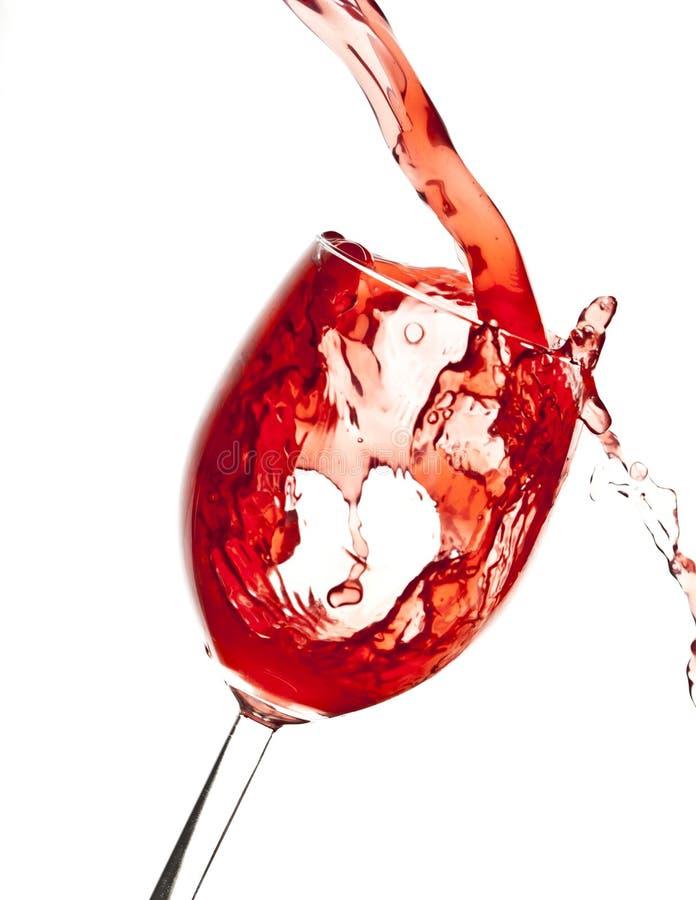 Hällande Cranberryfruktsaft i Wineexponeringsglas arkivfoto