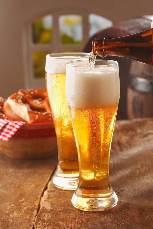 Hällande exponeringsglas av frothy öl arkivbild