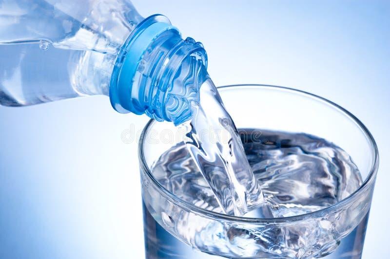 Hällande exponeringsglas för närbild av vatten från den plast- flaskan på blå bakgrund arkivbilder