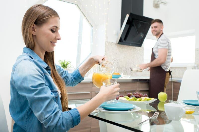 Hällande fruktsaft för glad kvinna medan manmatlagningfrukost royaltyfria foton