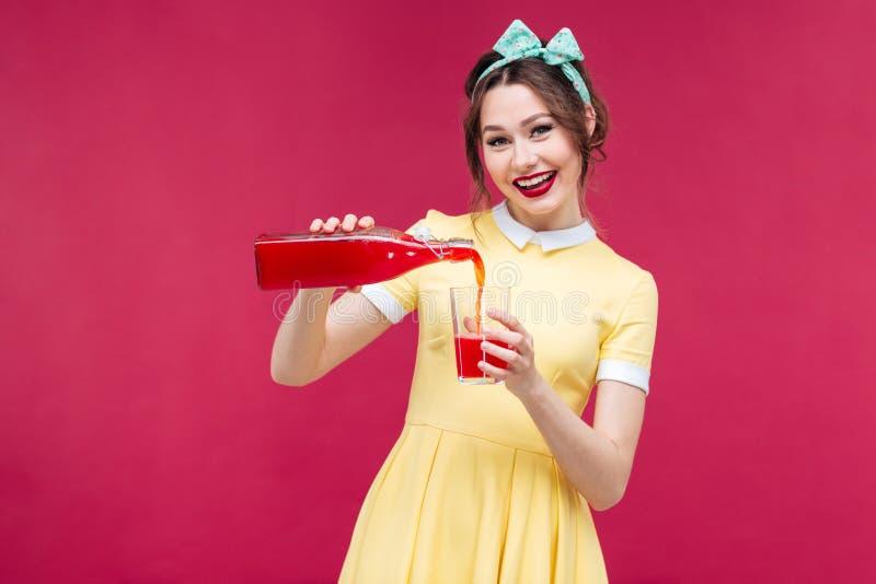 Hällande fruktsaft för gladlynt attraktiv kvinna från flaskan in i glaen arkivfoton