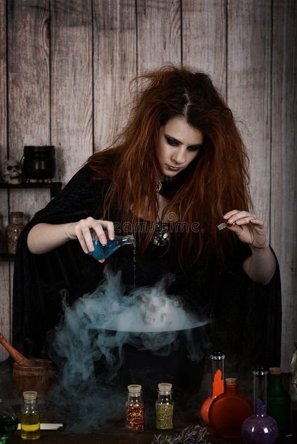 Hällande gift för häxa in i hennes magiska dryck med skallen i dimma royaltyfria bilder
