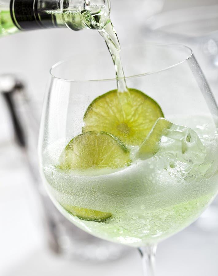 Hällande grön uppiggningsmedel i ett exponeringsglas med is- och limefruktskivor royaltyfri bild