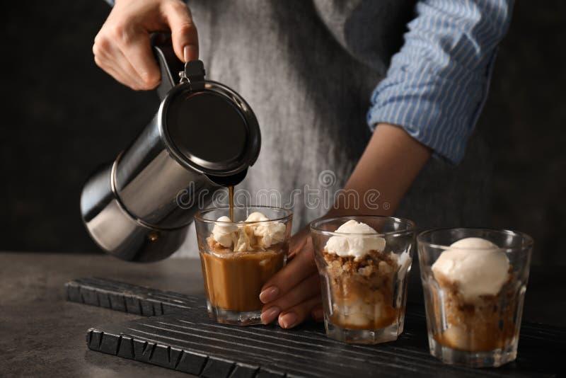 Hällande kaffe för kvinna in i exponeringsglas med glass arkivbilder