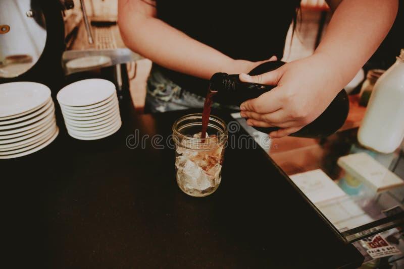 Hällande kaffe för kvinnlig barista in i en exponeringsglaskrus som fylls med is arkivfoton