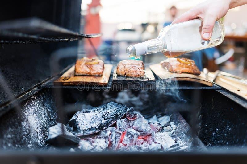 Hällande konjak för kockhand på laxen fotografering för bildbyråer