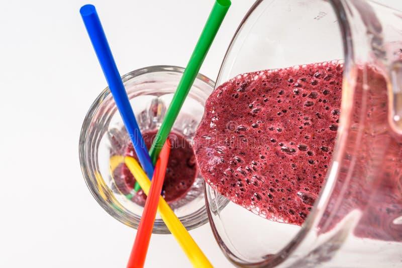 Hällande läcker rå smoothie in i ett exponeringsglas arkivfoton