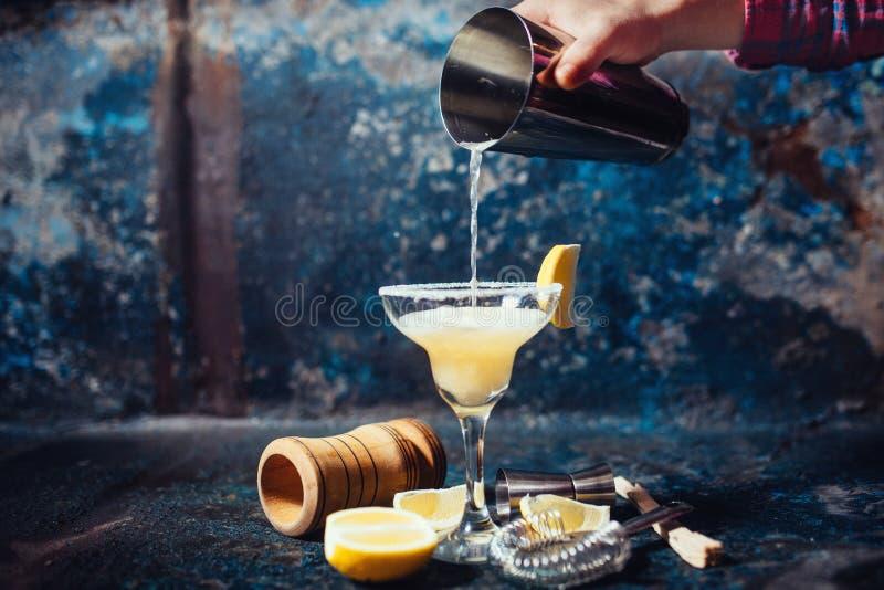 Hällande limefruktmargarita för bartender i utsmyckat exponeringsglas på restaurangen royaltyfri foto