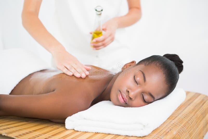 Hällande massageolja för massös på en nätt kvinnabaksida royaltyfri bild