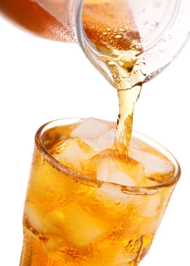 Hällande med is te in i exponeringsglas med is från kruset royaltyfria foton
