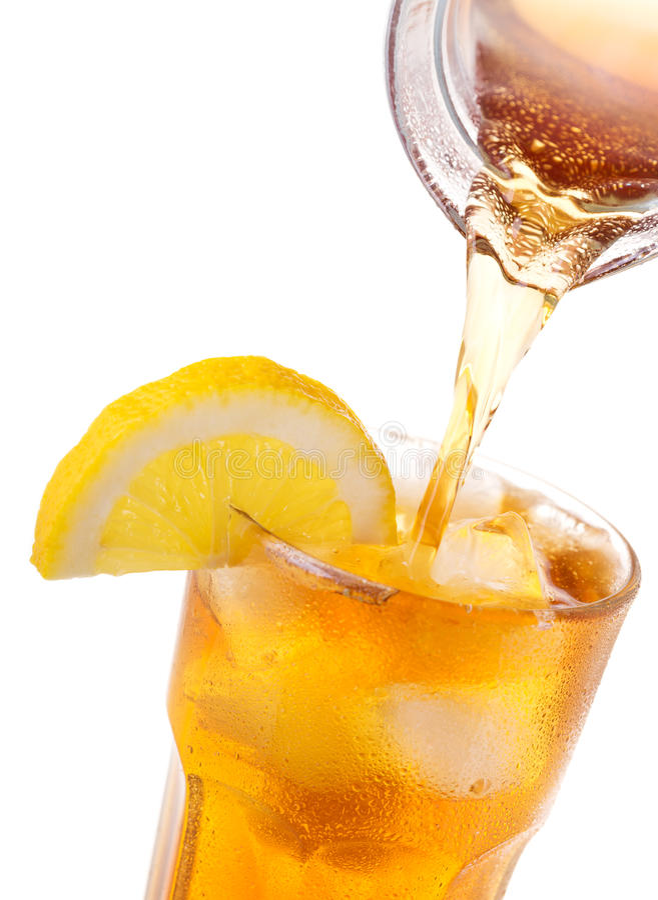 Hällande med is te in i exponeringsglas med is och citronen royaltyfria foton