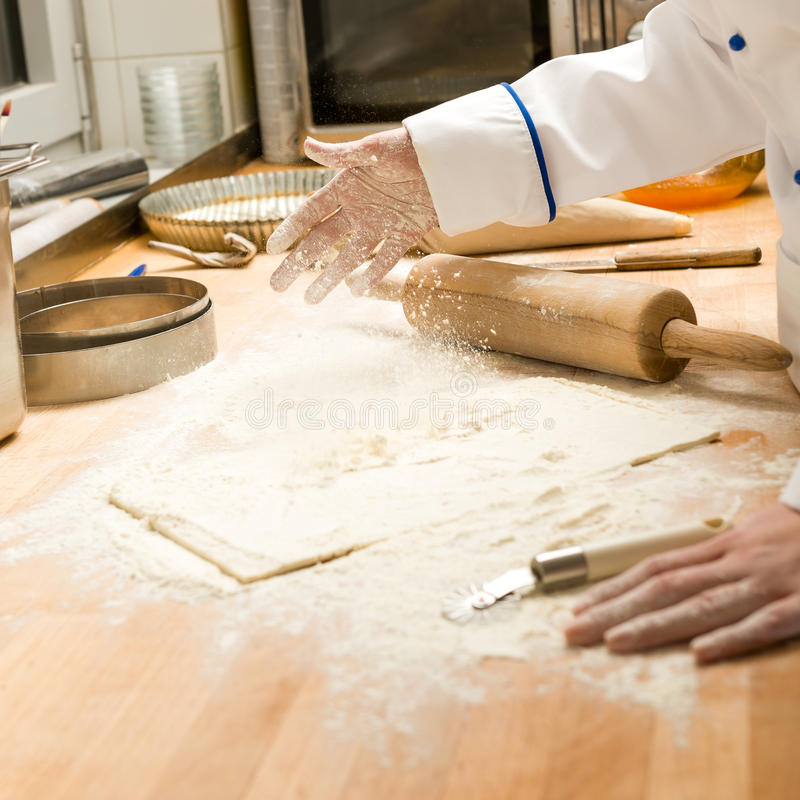 Hällande mjöldeg och kavel för kock arkivbilder