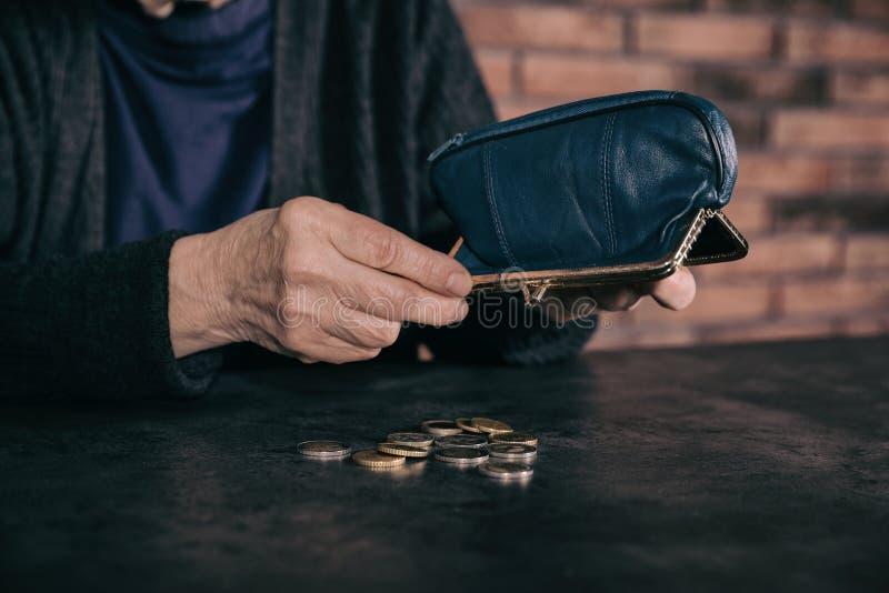 Hällande mynt för fattig mogen kvinna ut ur plånboken på tabellen arkivbilder