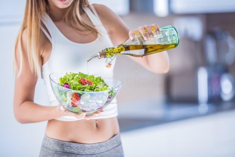 Hällande olivolja för kvinna in till grönsaksalladen royaltyfri bild