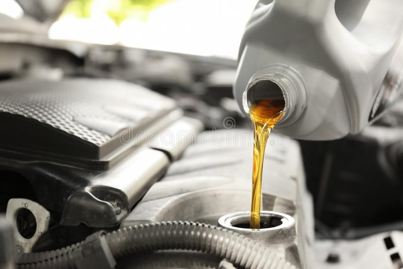 Hällande olja in i bilmotorn royaltyfria foton