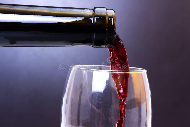 hällande rött vin för flaska royaltyfria bilder