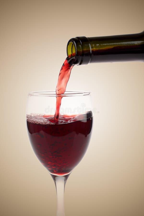 hällande rött vin för flaskexponeringsglas arkivfoto