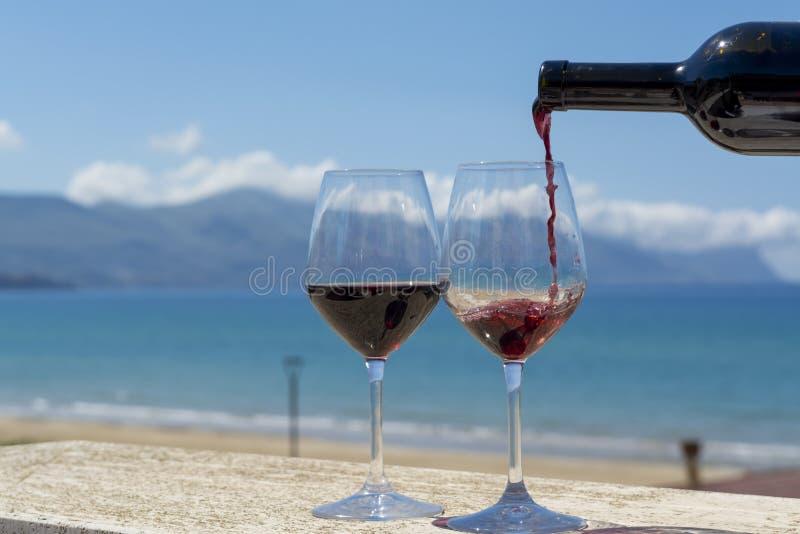 Hällande rött vin för uppassare i vinexponeringsglas på sikt för hav och för berg för utomhus- terrasswitn blå på bakgrund royaltyfria bilder