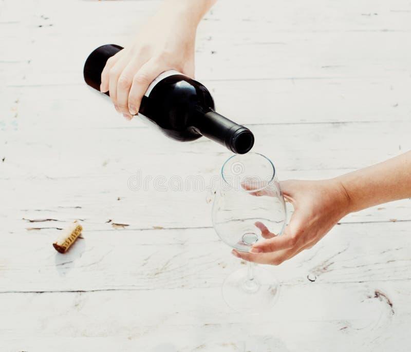 Hällande rött vin från flaskan i tomt vinexponeringsglas på vitt trä royaltyfri bild