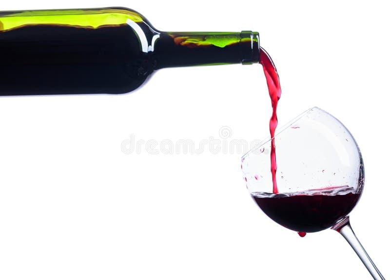 Hällande rött vin från flaskan till exponeringsglas som isoleras på vit arkivbild