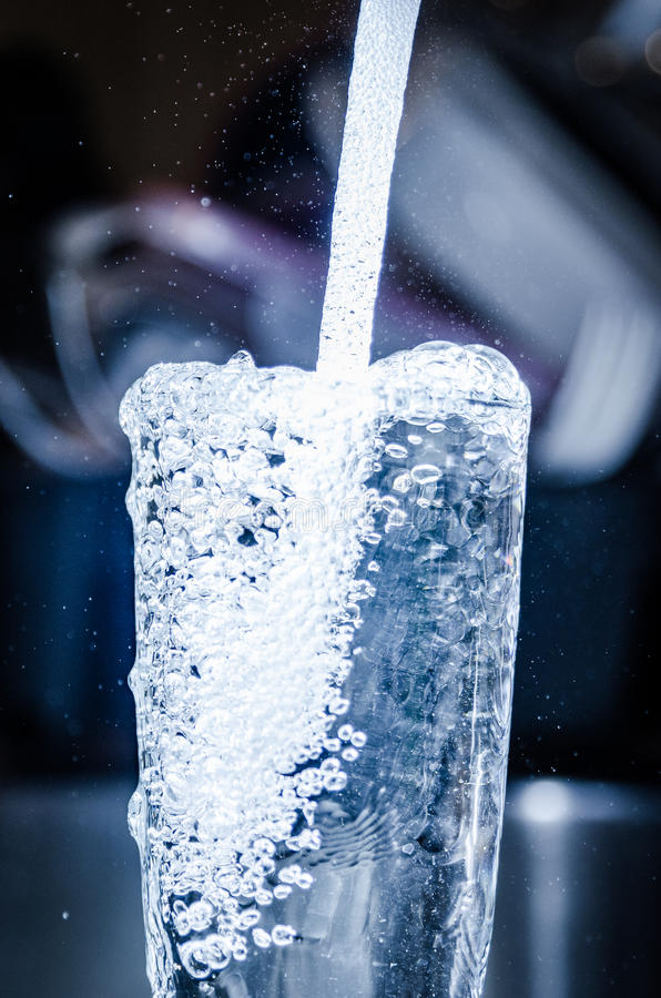 Hällande rent säkert dricksvatten från klapprörhem royaltyfri foto