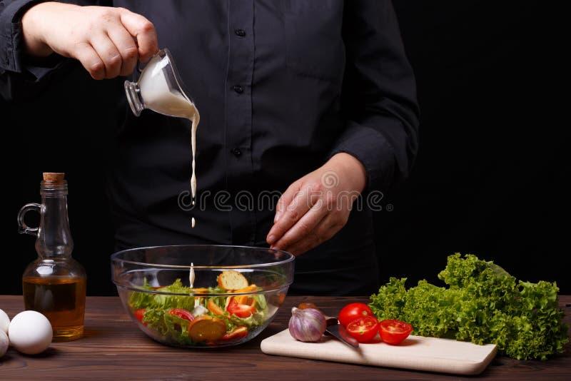 Hällande sås för kock på caesar sallad, matlagningprocess, restaurang arkivbilder