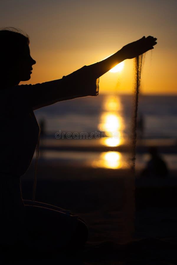 Hällande sand för flicka på solnedgången royaltyfria foton