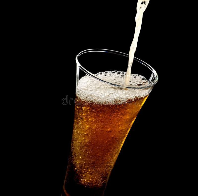 Hällande skum in i ett exponeringsglas av kallt öl på en svart bakgrund arkivfoto