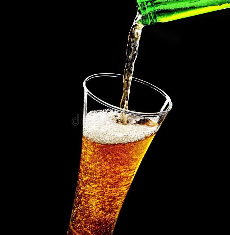 Hällande skum in i ett exponeringsglas av kallt öl på en svart bakgrund royaltyfri foto
