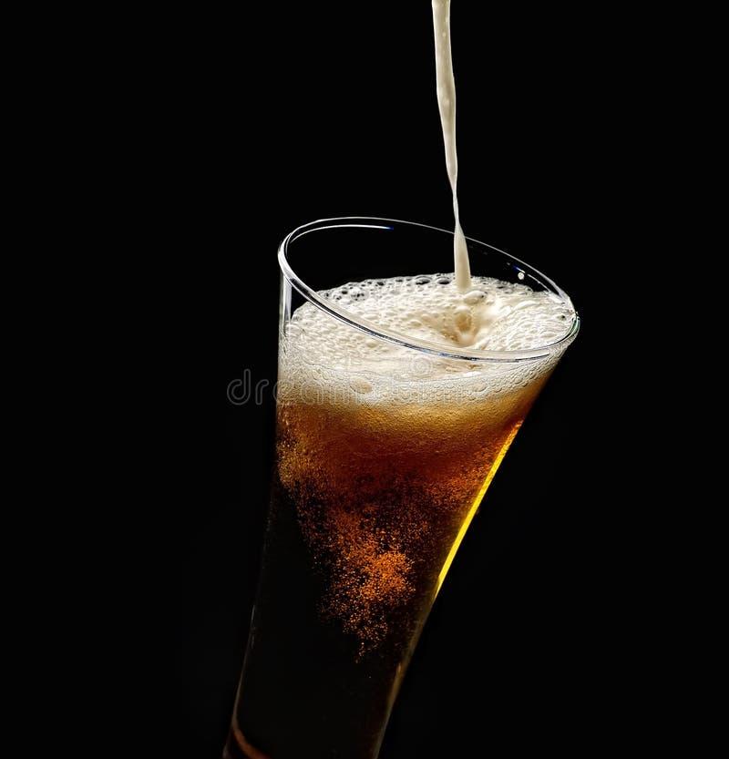 Hällande skum in i ett exponeringsglas av kallt öl på en svart bakgrund arkivbilder