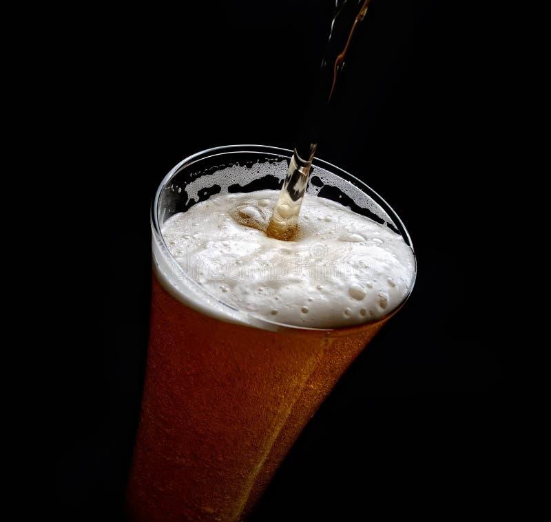 Hällande skum in i ett exponeringsglas av kallt öl på en svart bakgrund royaltyfri fotografi