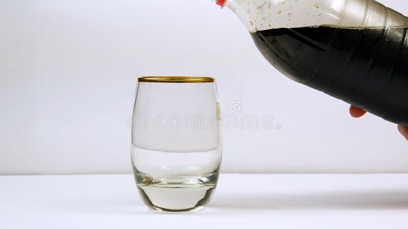 Hällande sodavatten från flaskan in i ett exponeringsglas arkivbilder
