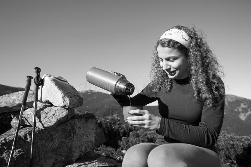 Hällande te för flickafotvandrare ut ur termoset svart white royaltyfri foto
