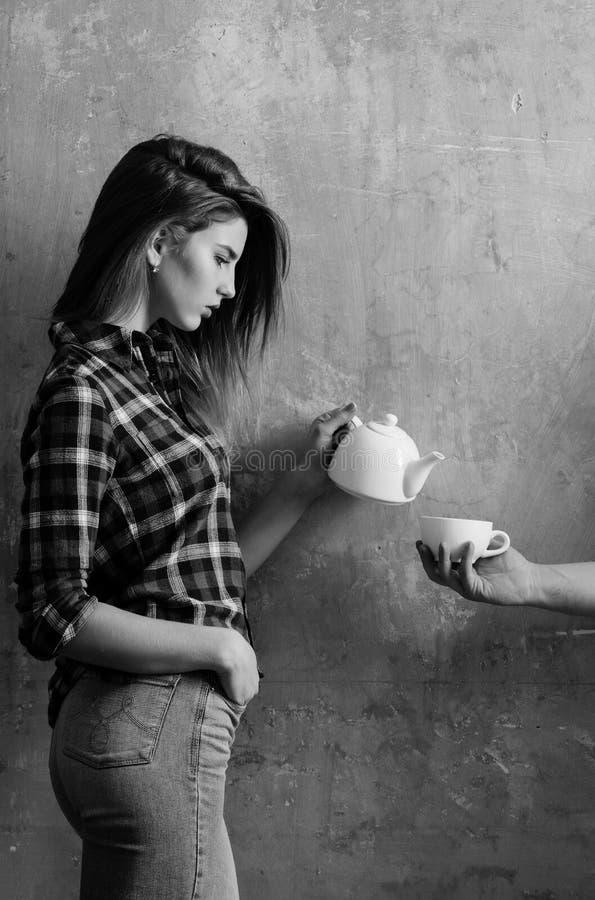 Hällande te för nätt flicka som ska kupas i den manliga handen arkivbild