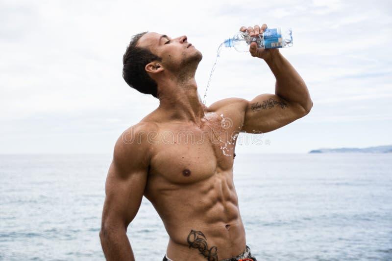 Hällande vatten för attraktiv shirtless muscleman på hans bröstkorg från den plast- flaskan royaltyfria foton