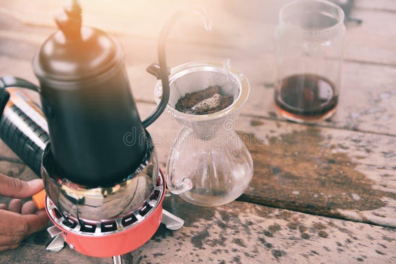 Hällande vatten för droppandekaffebarista på filtrerat brygga - som gör kaffe för kopphanddroppande i exponeringsglaskrus på vägn royaltyfri bild