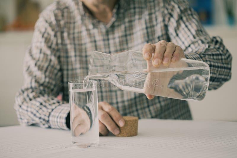 Hällande vatten för gamal man från flaskan till exponeringsglas i kök arkivbilder