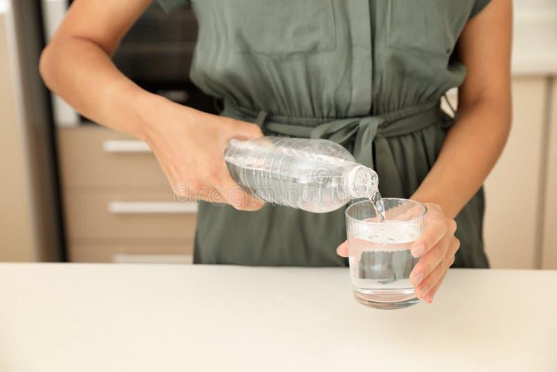 Hällande vatten för kvinna från flaskan in i exponeringsglas i kök arkivbild