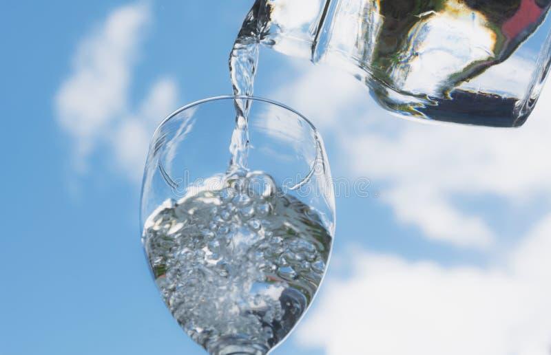 Hällande vatten för kvinnlig hand från flaskan till exponeringsglas fotografering för bildbyråer