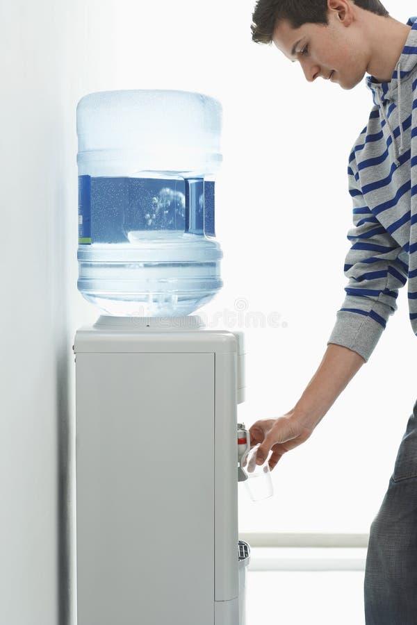 Hällande vatten för man från kylare royaltyfri bild