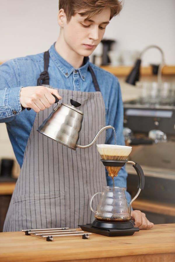 Hällande vatten för manlig barista till och med jordning som gör pouroverkaffe royaltyfri foto